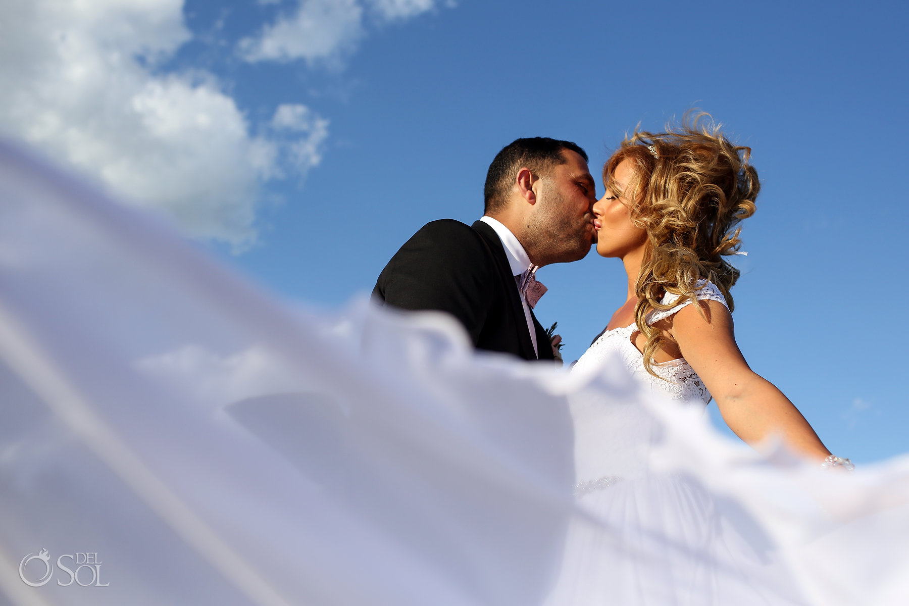 groom and bride passionate kiss portrait Blue sky