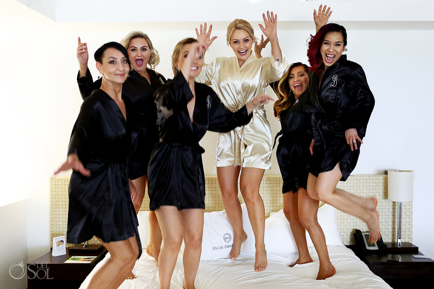 bride jumping on bed with bridesmaids getting ready photo ideas
