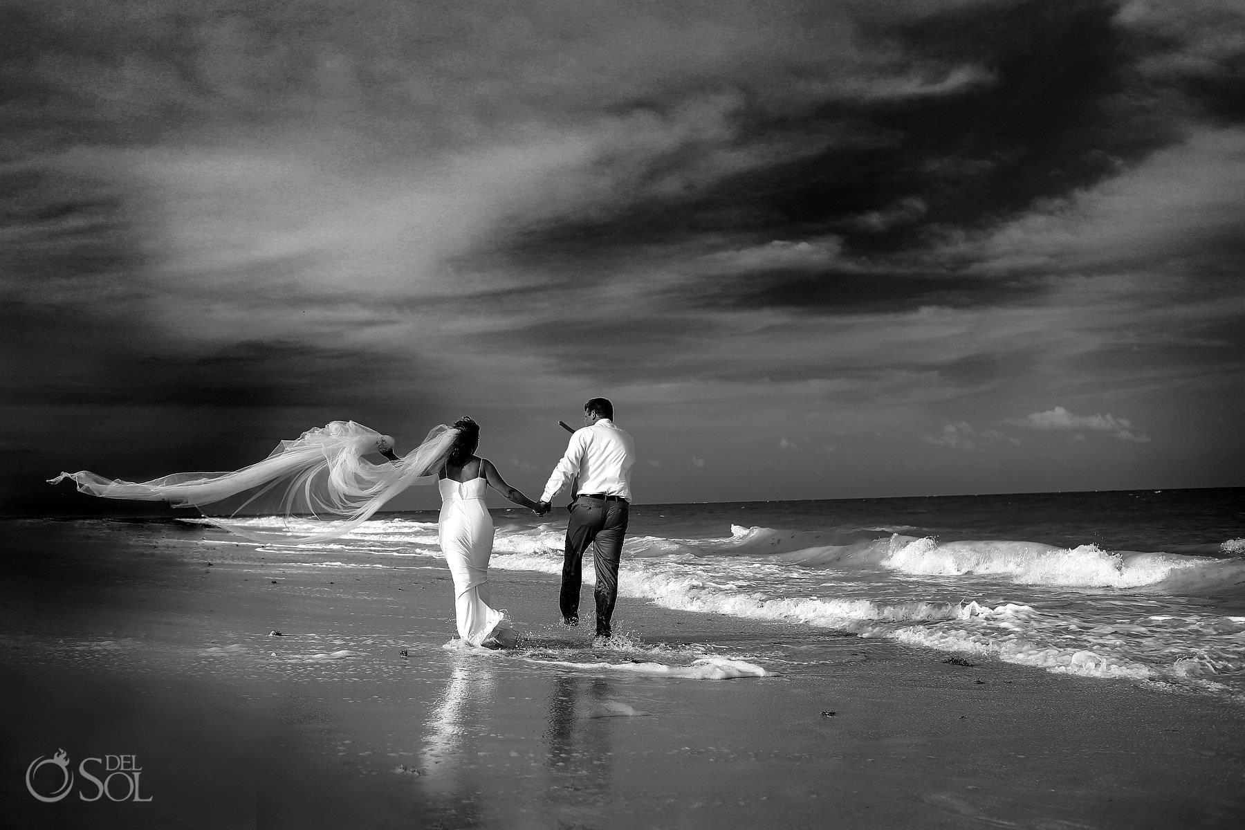 bride and groom running on the beach Isla Blanca Cancun trash the dress