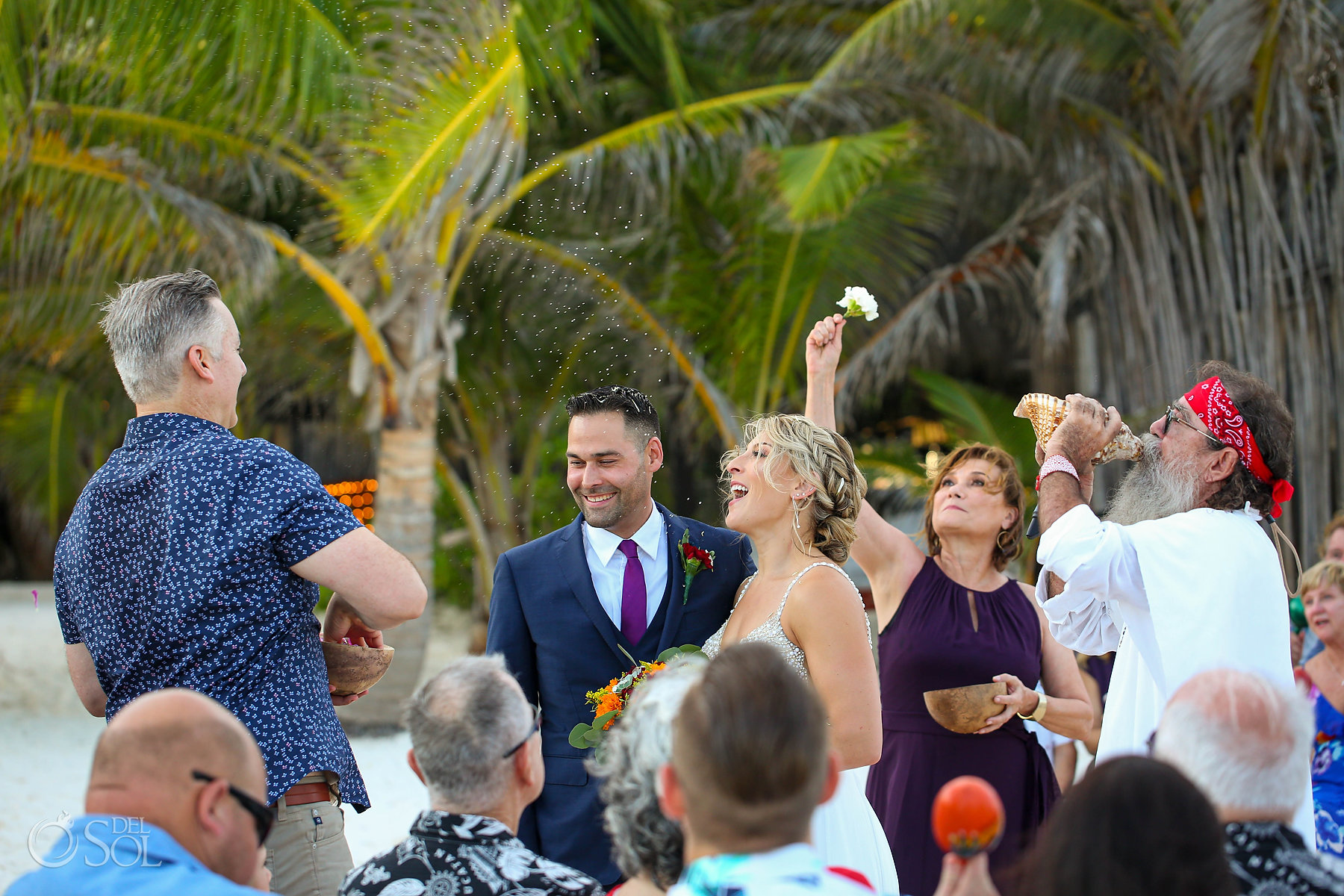 Bride laughing as guests throw flower petals cosmic wedding ceremony Akiin Tulum Mexico