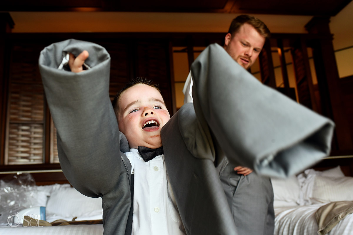 funny wedding photo ringbearer trying on suit jacket kids will be kids