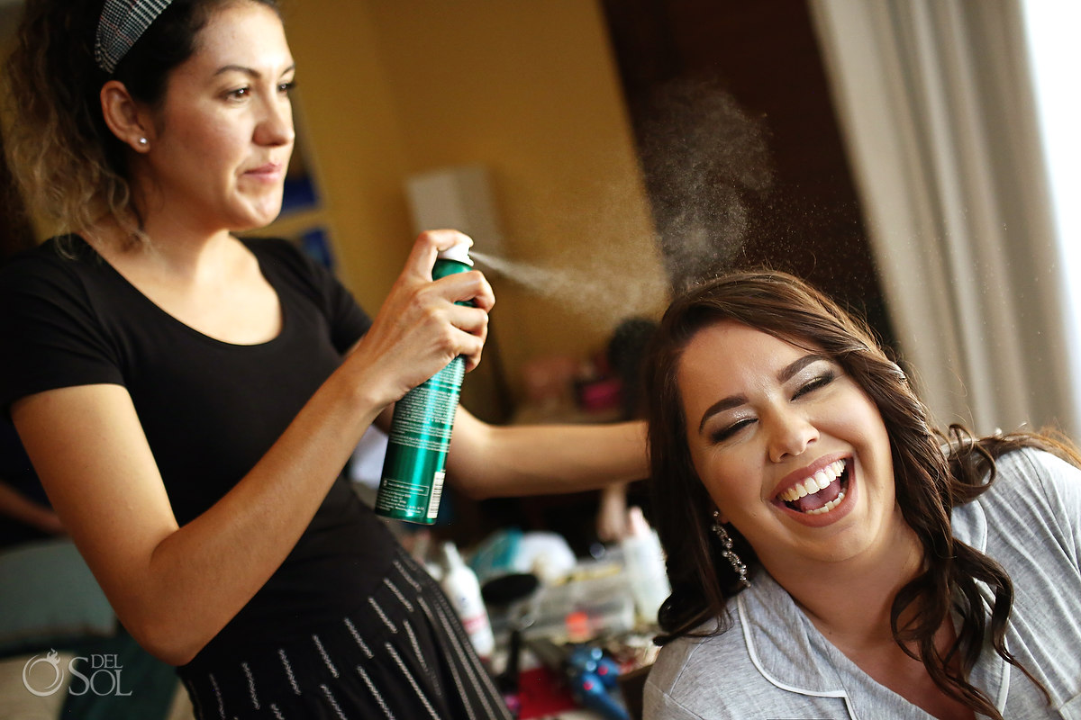 bridal hair and makeup bride laughing with hair spray