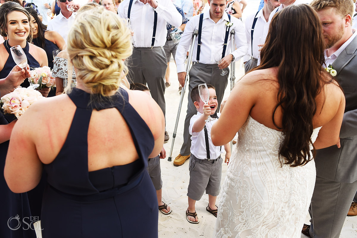 ringbearer gives champagne toast cheers to bride and groom