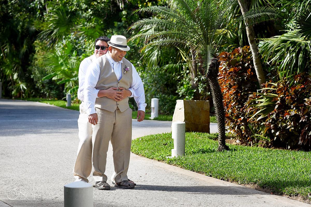 funny wedding photogroomsman hugs groom waiting for first look