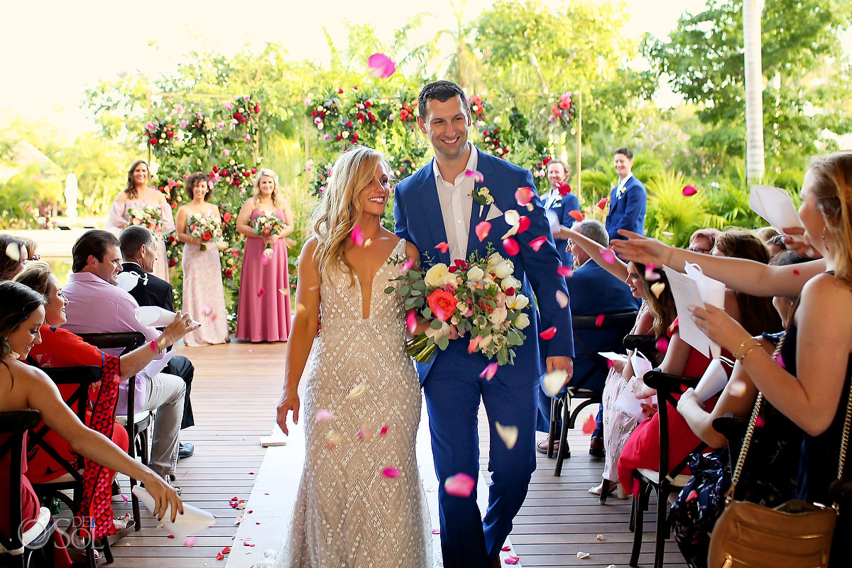 couple exit throwing rose petals Secrets Akumal Arch Wedding Riviera Maya Mexico