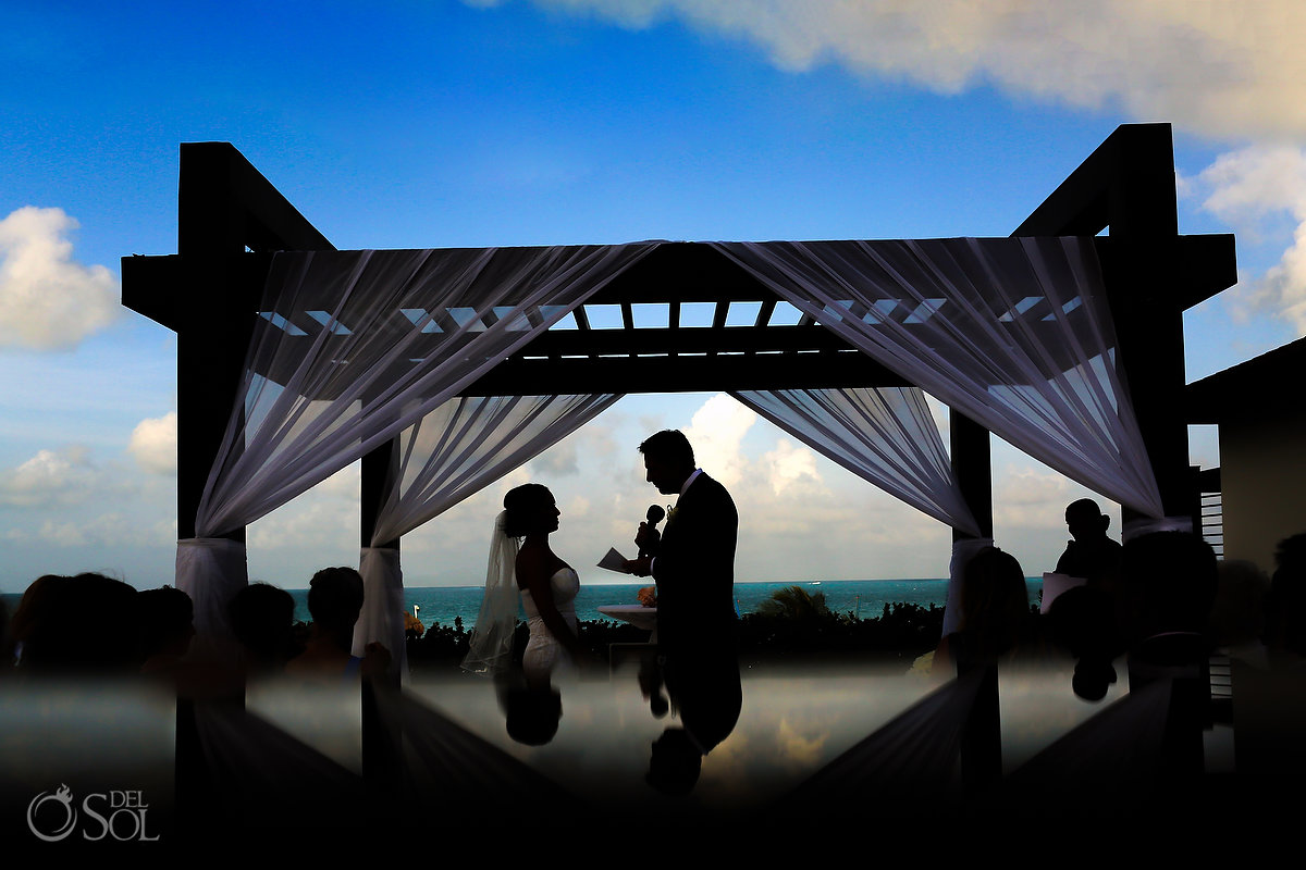 groom reading vows silhouette Secrets laya Mujeres Gazebo Cancun