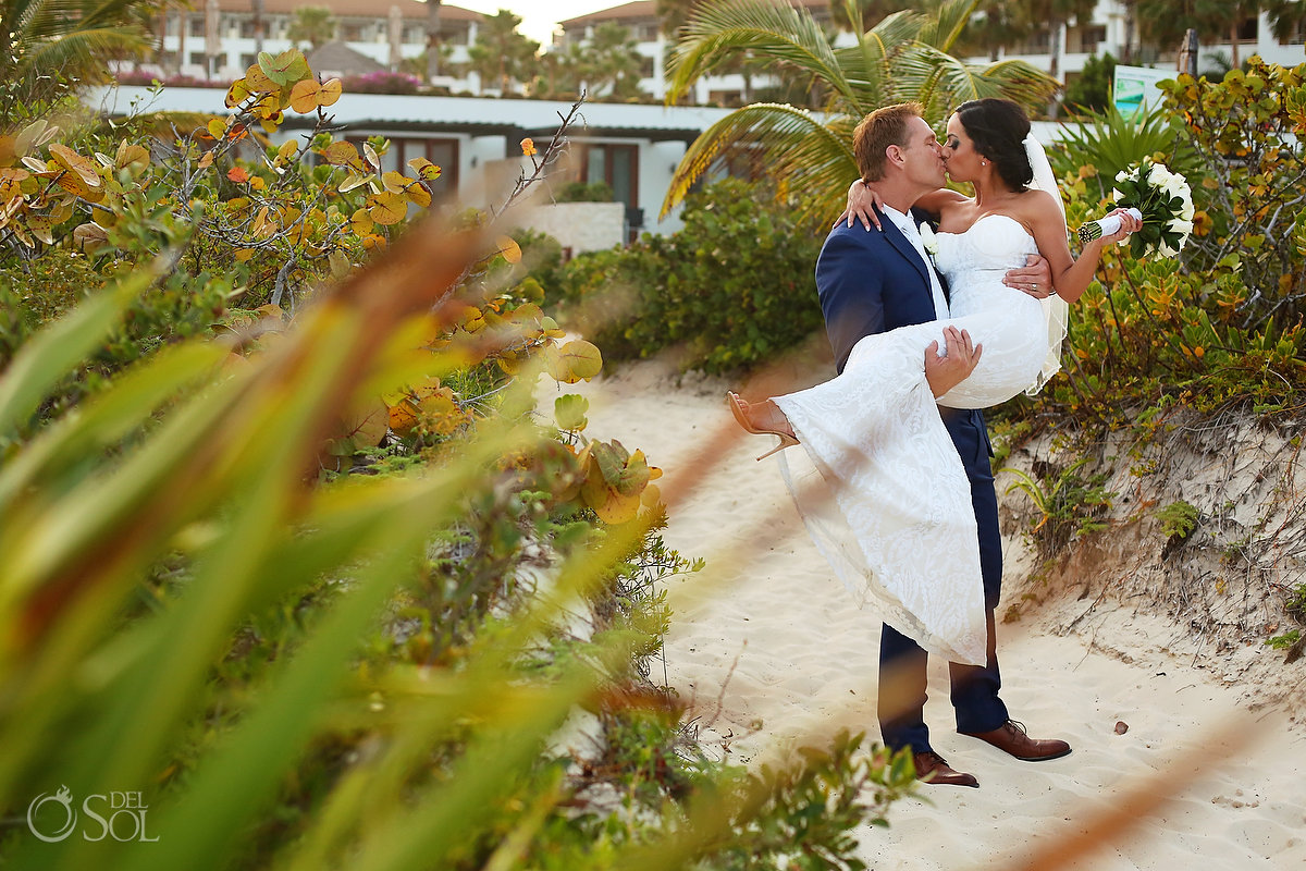 groom carring bride kissing her on the way to the beach Secrets Playa Mujeres