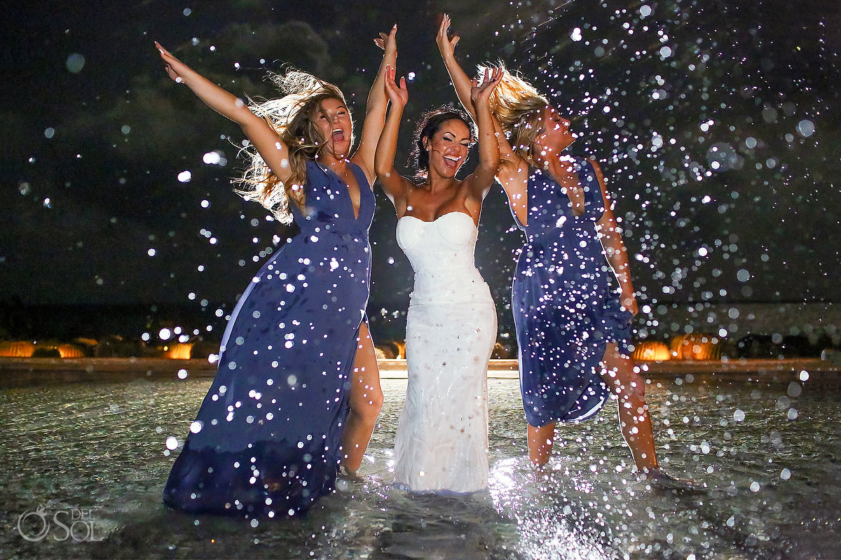 bride and bridesmaids jump in the pool Secrets Playa Mujeres Cancun