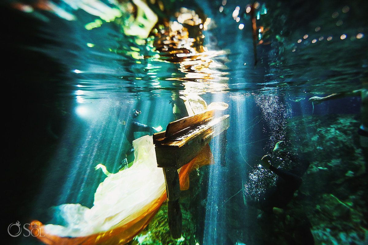 underwater driftwood piano in rays of light mexico cenote Cancun