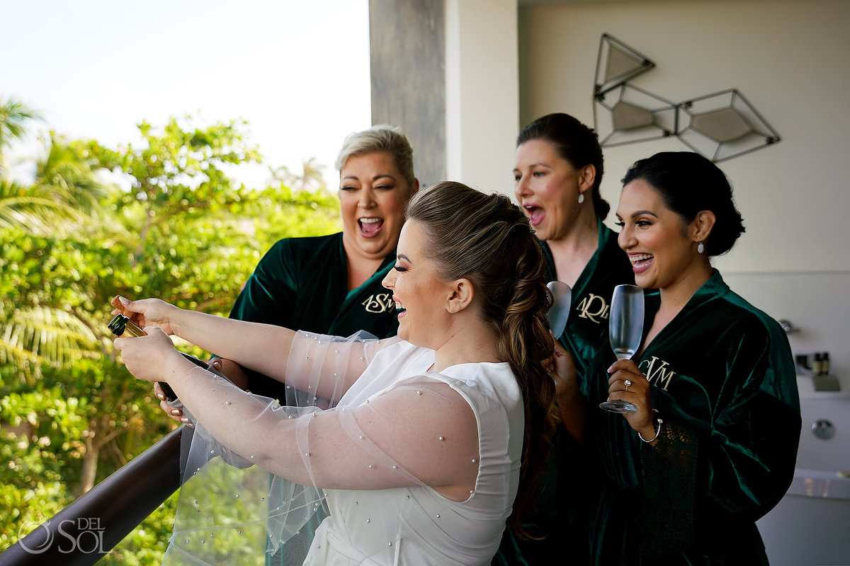 bride and bridesmaid opening champagne wearing custom green velvet robes