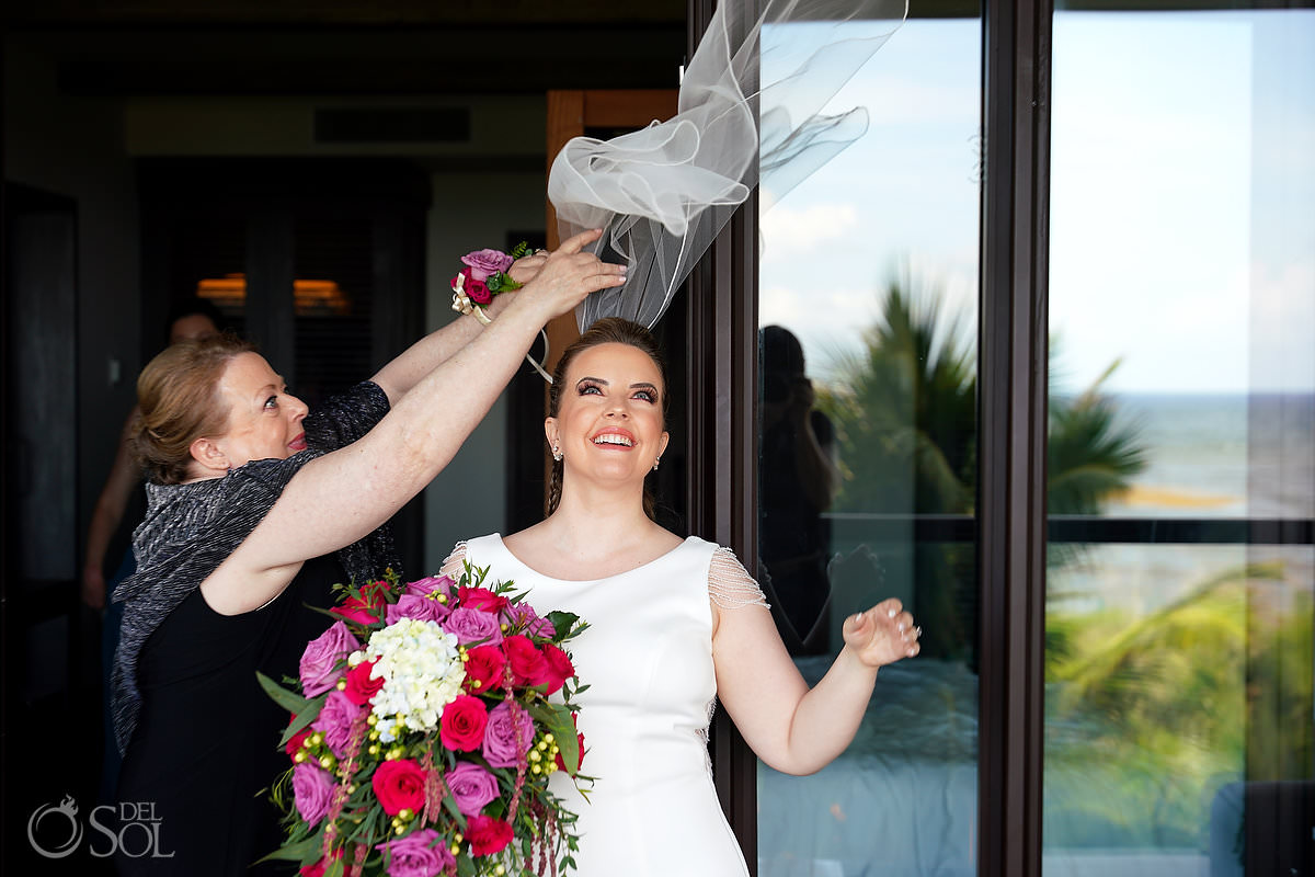 mom putting on brides wedding veil flying away in the wind