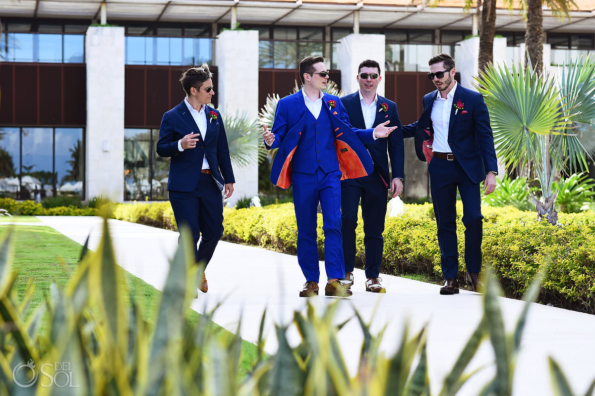 groom and groomsmen wearing navy and royal blue suits with bright orange and pink linings